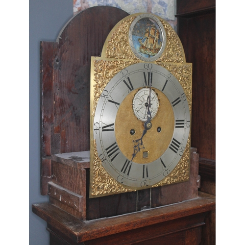 12 - A Georgian oak eight day longcase clock, the hood with arched top, three brass finials and brass ter...