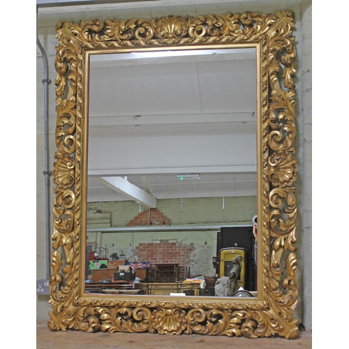 15 - A large continental 19th century giltwood and gesso mirror of rectangular form with pierced acanthus...