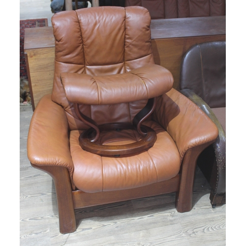 21 - A Norwegian Ekornes Stressless tan leather reclining armchair and footstool....