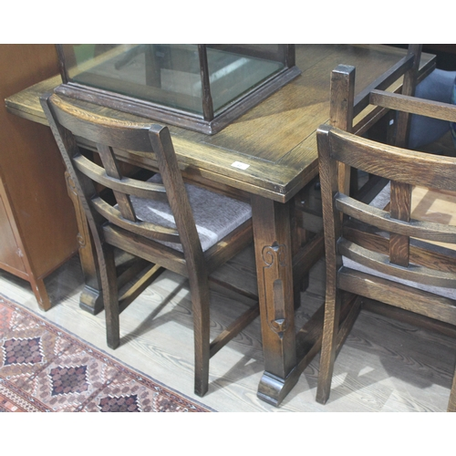 42 - An oak drawer leaf table with carved legs and four matching chairs....