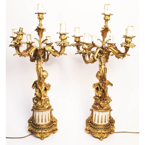 7 - A pair of French gilt bronze candelabra, each formed as a cherub, one reading and the other studying...