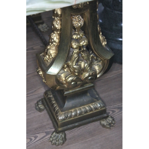 16 - An onyx top occasional table with gilt metal twin pedestals each with platform base and claw feet, l...