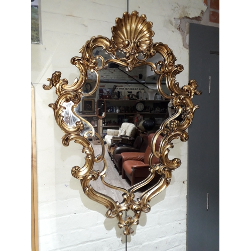 100A - A gilt wood and gesso ornate mirror, height 120cm, width 87cm....