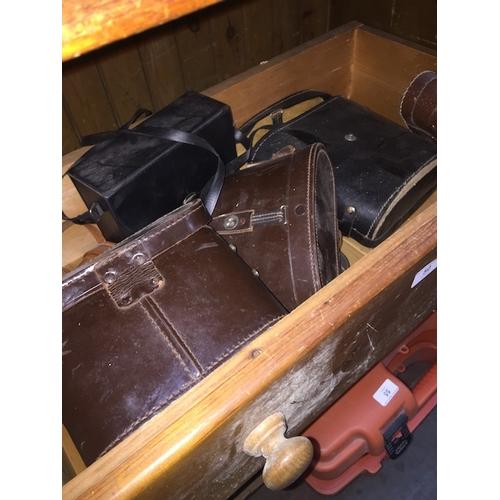 50 - A wooden drawer of cased binoculars...
