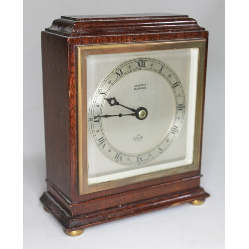 3 - An Elliot clock, mahogany case with brass bun feet, silvered dial with Roman numerals, height 15cm....