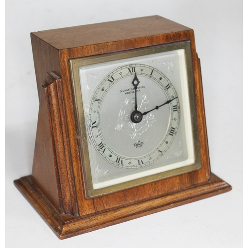4 - An Elliott clock, Art Deco style walnut case and silvered dial with rosette and retailer's mark 'Oll...