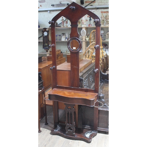 36 - A Victorian mahogany arched top gothic hall stand with turned hooks, singular round mirror, lidded b...