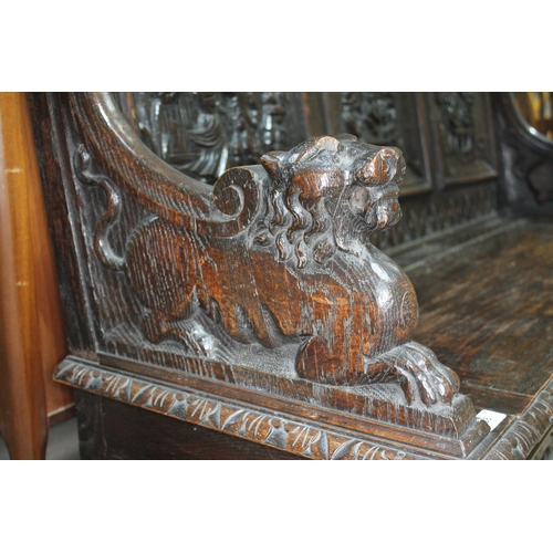 38 - A 19th century carved oak settle with lion arms, carved continental scene panels to back, lift top s...