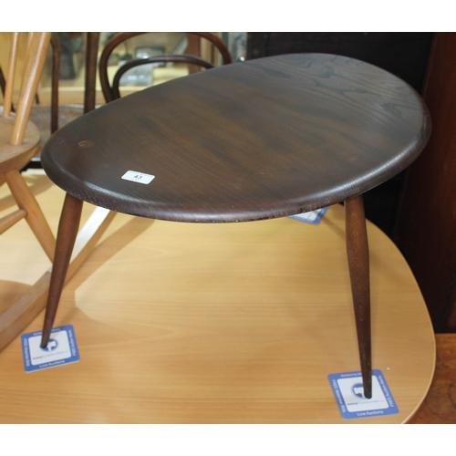 43 - A dark elm Ercol single pebble table, height 40cm, width 66cm....