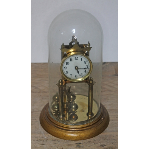 34 - A brass revolving pendulum clock under glass dome, dial diam. 8cm, height of dome approx. 32cm....