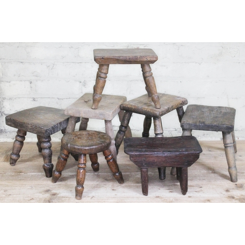 57 - A group of seven wooden milking stools, heights ranging from 18cm to 26cm.