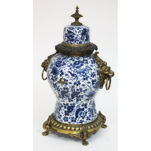 7 - A 19th century French faience blue and white and gilt metal mounted clock, with lion mask handles to...