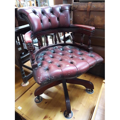 852 - A reproduction red buttoned and studded leather captain's swivel chair....