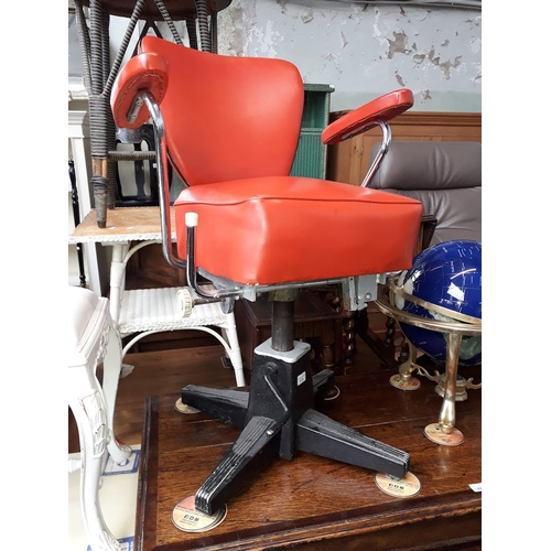 876 - An American style chrome barber's chair with red vinyl upholstery....