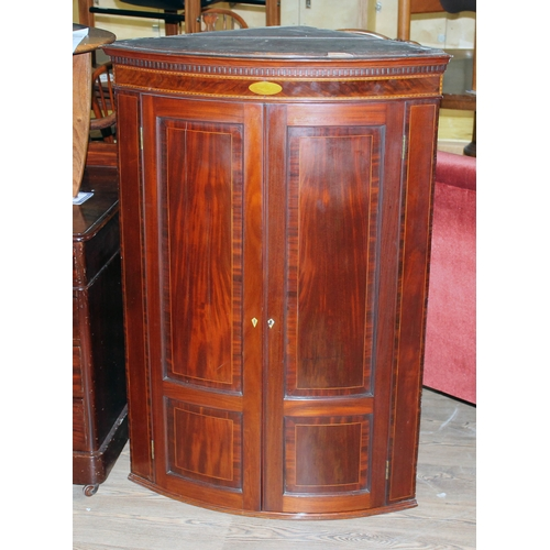 23 - A George III bow front inlaid mahogany corner cabinet with dentilated moulding, shell inlay and pane...