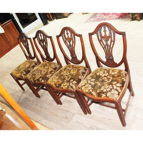 24 - A set of four George III mahogany chairs in the manner of Hepplewhite with shield backs carved with ...