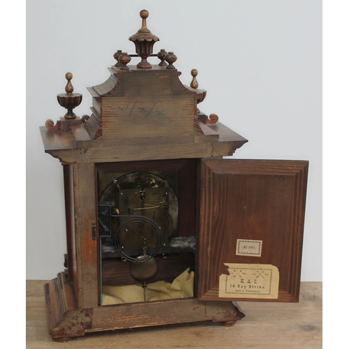 30 - A German late 19th century walnut mantle clock of architectural form with pagoda top, finials, bobbi...