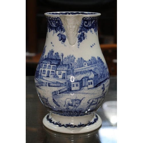 322 - An 18th century blue and white jug with mask spout, scroll handle, the body decorated in blue and wh...