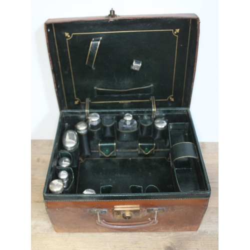 358 - A leather case by Finnigans Manchester fitted with matched hallmarked silver topped bottles....