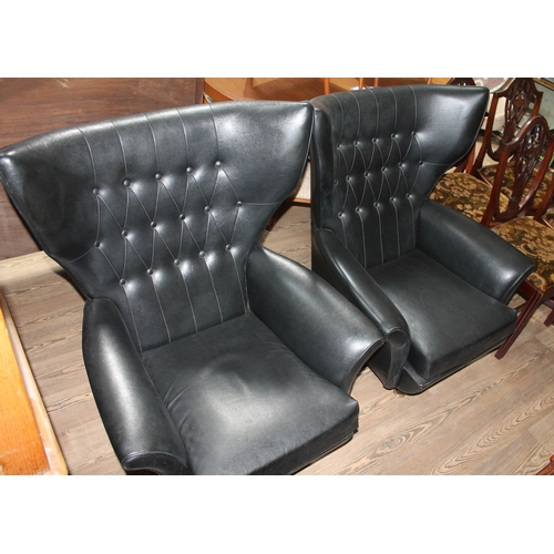 38 - A pair of G-Plan 'Blofeld' black rexene retro swivel armchairs with arched buttoned wing back above ...