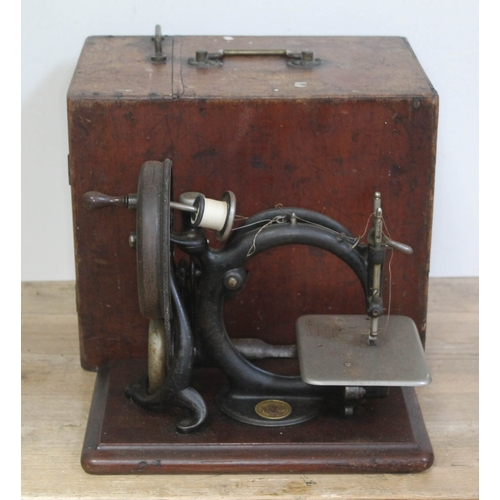 393 - A Willcox & Gibbs hand cranked sewing machine with wooden case....