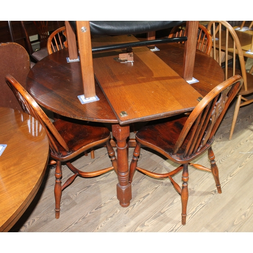 4 - An oak extending dining table with one leaf and four spindle back and elm seated chairs with crinoli...