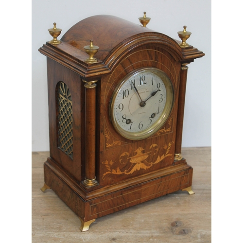 68 - An Edwardian walnut mantle clock with domed top, brass finials, marquetry inlay, columns, fish grill...