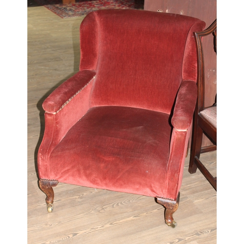 7 - A late Victorian armchair by Gillows, upholstered in red, oak cabriloe legs and brass castors, rear ...