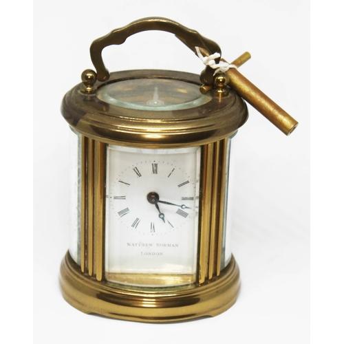 403 - A Matthew Norman miniature brass carriage clock of oval form, height 10cm....