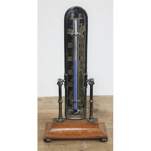 437 - A silver plated thermometer on oak base, height 37cm....