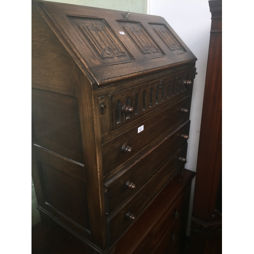 857 - A priory style oak bureau with linen fold panels...