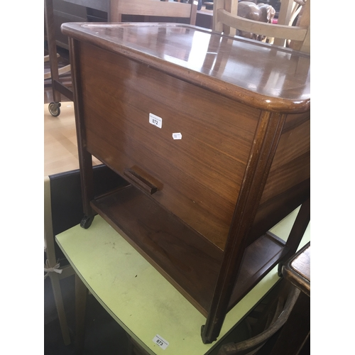872 - A walnut sewing cabinet on castors...