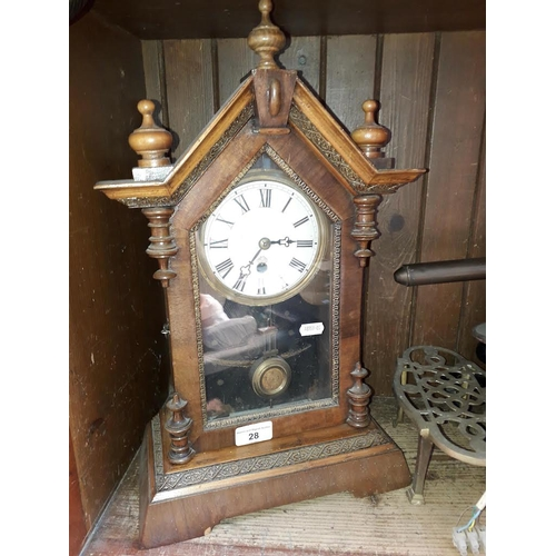 28 - A wooden cased mantle clock with pendulum and key...