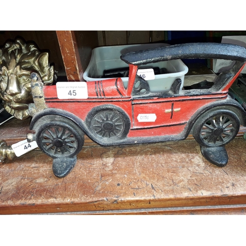 45 - A cast foot scraper in the form of a vintage car and a brass post horn in 2 parts...