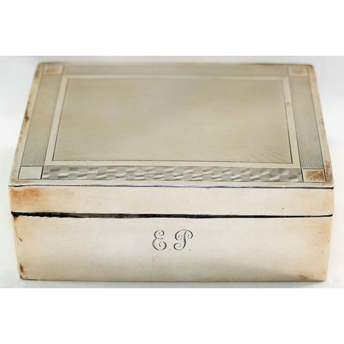 138 - A George V silver cigarette box, Birmingham 1925, with engine turned decoration and wooden lined int...
