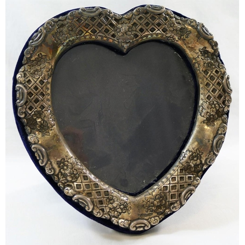 145 - A silver heart-shaped picture frame, London 1988, the undulating frame embossed with scroll, floral ...