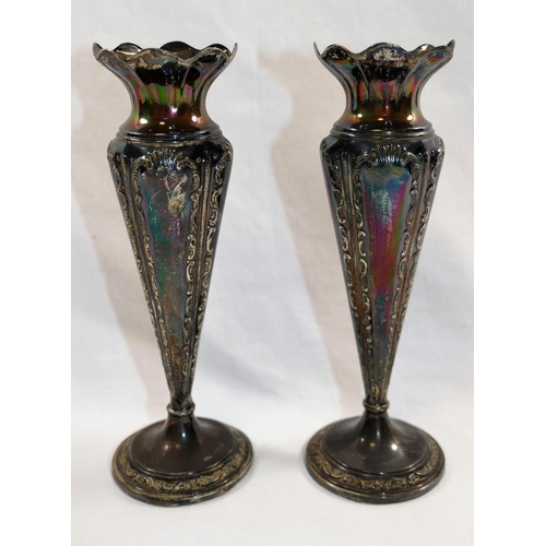 158 - A pair of small Edwardian silver vases, with flared rims and scroll decoration, raised on circular f...