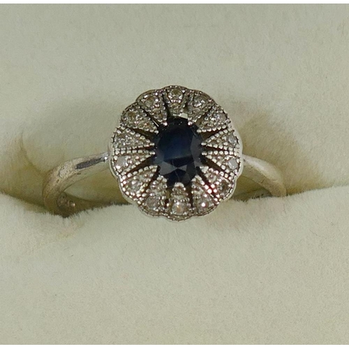 182 - A sapphire and diamond oval cluster ring, the shank stamped '925', finger size O 1/2, and a silver s...