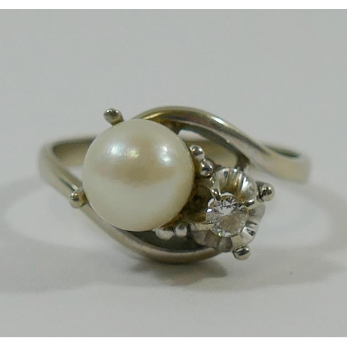 188 - A cultured pearl and diamond cross over ring, the round brilliant cut diamond approximately 0.08 car...