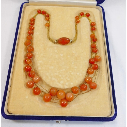 196 - A carnelian and yellow metal four strand necklace, each strand comprised of a fine yellow metal chai...