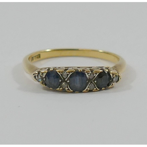 199 - An 18 carat gold sapphire and diamond carved half hoop ring, the three oval mixed cut sapphires set ...