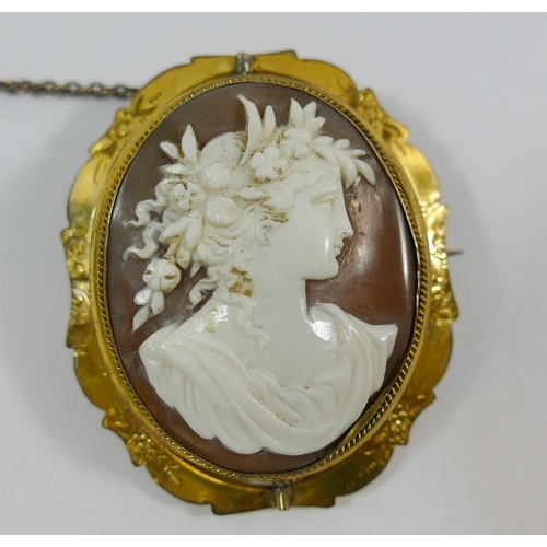 201 - A Victorian carved shell cameo in pinchbeck brooch mount, carved with the head of the Roman fertilit...