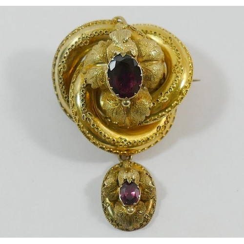 204 - A Victorian gold and garnet set pendant brooch, the hollow brooch of stylised knot form overlaid wit...