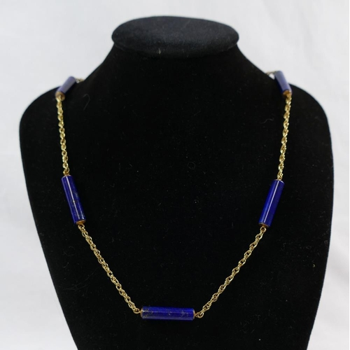205 - A yellow metal and lapis lazuli necklace, the chain incorporating seven cylindrical lapis lazuli bar...
