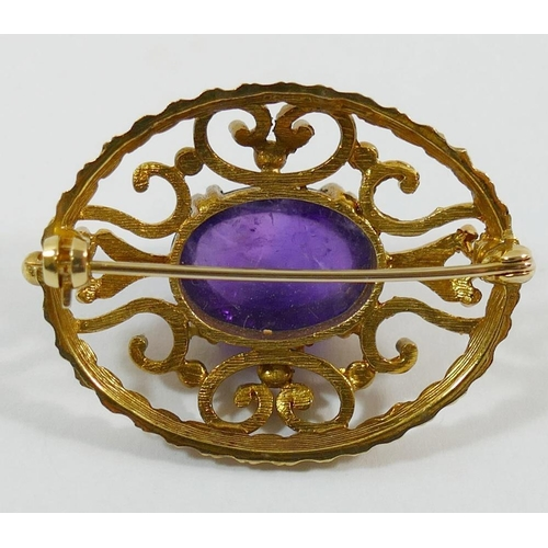 211 - A 9 carat gold oval openwork brooch set with a single cobochon amethyst, 3.6cm x 2.8cm, 10.5g gross...