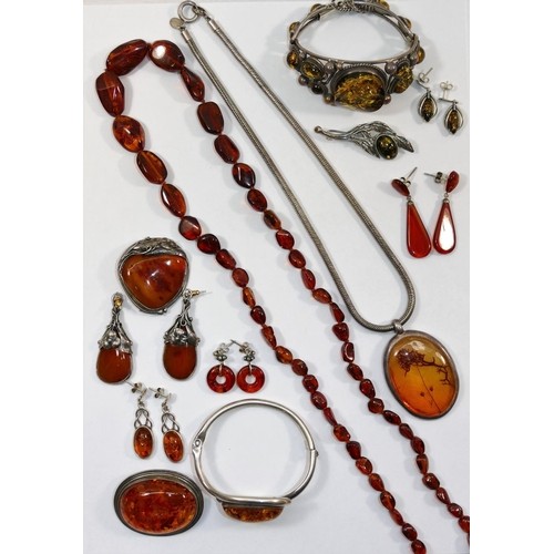 219 - A silver and amber brooch and earrings suite, with floral mounts, housed in unassociated fitted box,...