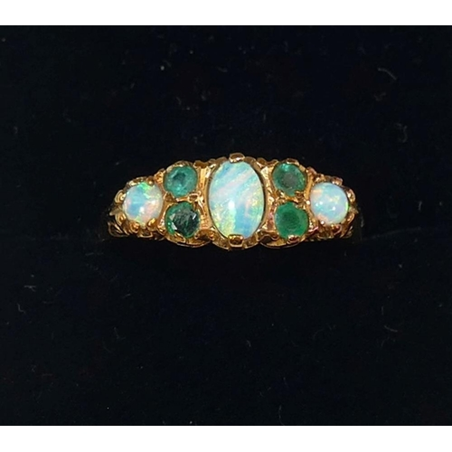 225 - A 9 carat gold opal and emerald Victorian style carved half hoop ring, the three oval opal cabochons...