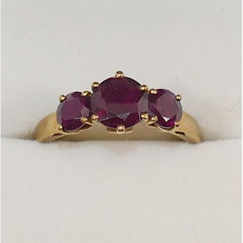 231 - A 9 carat gold almandine garnet three stone ring, the round mixed cut garnets in claw settings, the ...