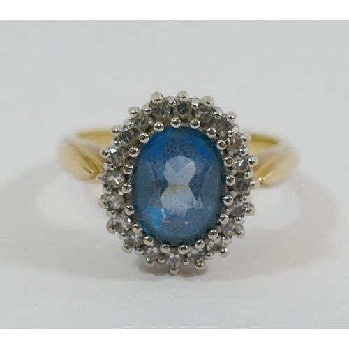 235 - An 18 carat gold topaz and diamond oval cluster ring, London 1989, the oval mixed cut topaz within 2...