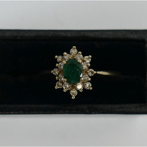 243 - A 9 carat gold emerald and diamond cluster ring, with import marks for London 1987, the oval mixed c...